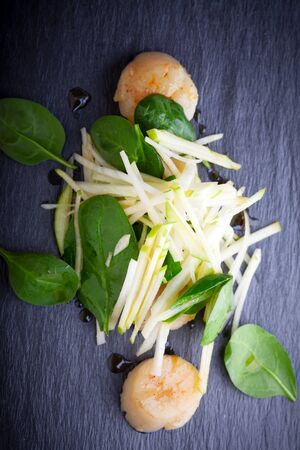 Scallop salad with apple, spinach on a stone plate.