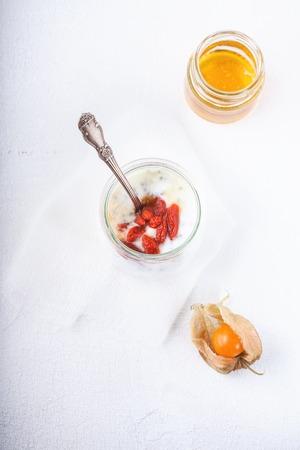 processed grains: Yoghurt with goji berries, chia seeds and honey Stock Photo