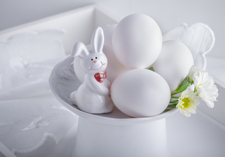 Eggs Rabbit and flowers on white surface