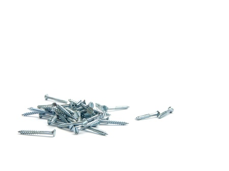 Several flat head screws pilled over each other laying down on white background photo
