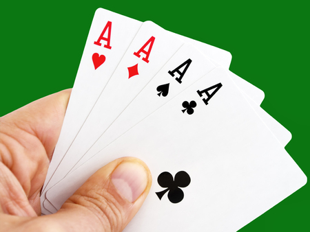 Man hand holding four aces on green background with clipping path
