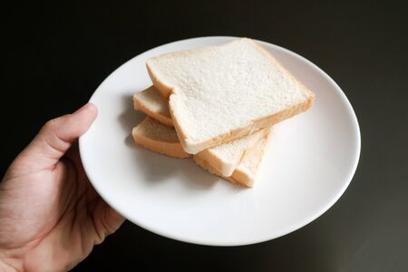 Toasted 3 slice on the your hand in black backgroud Reklamní fotografie