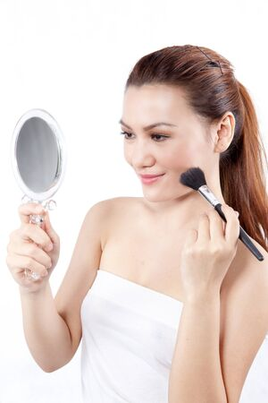 asian woman applying make up on her face using a brush while holding a mirror photo
