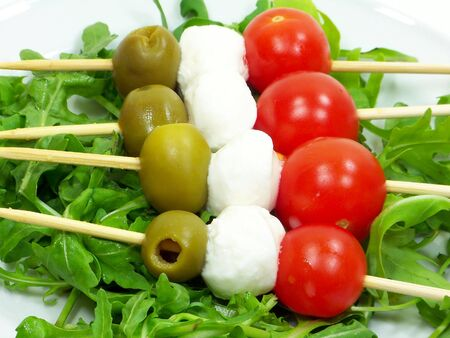 Italian kebabs with mozzarella cheese olives and tomatoes over rocket bed