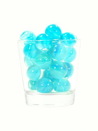 distortion: Light blue marbles in a glass isolated over white background