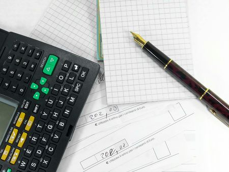 Fountain pen calculator notepad and bills over white Stock Photo