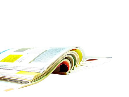 Stack of open magazines isolated over white background photo