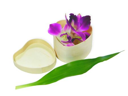 Heart-shaped wood box with orchids inside isolated over white background photo