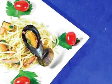 Spaghetti with seafood parsley and tomatoes over blue background photo