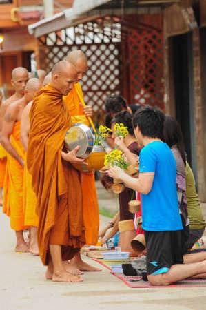 17: Chiang Khan, Tailandia - el 17 de julio: Un hombres no identificados da ofrendas de alimentos y flores a un monje budista el 17 de julio de 2011 en Chiang Khan, provincia de Loei, Tailandia. Tailand�s tradicional, gente har� hacer m�rito por dar comida a monje
