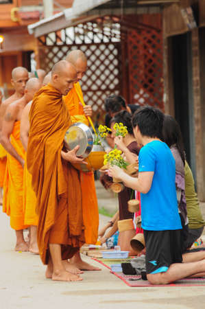 loei: Chiang Khan, THAILAND - July 17: An unidentified men Gives food and flower offerings to a Buddhist monk on July 17, 2011 in Chiang Khan, Loei province, Thailand. Thai traditional, people will make merit making by give food to monk