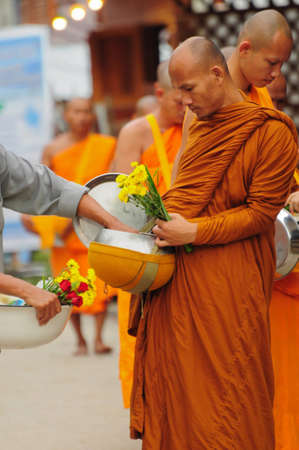 Chiang Khan, Thailandia - 17 luglio: Una non meglio identificata uomini d� cibo e fiore offerte a un monaco buddhista su 17 luglio 2011 in Chiang Khan, provincia di Loei, Thailandia. Thai tradizionale, persone far� fare al merito da dare cibo a Monaco Editoriali