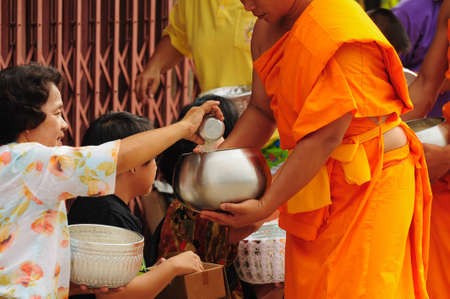 Chiang Khan, THAILAND - July 16: An unidentified men Gives food and flower offerings to a Buddhist monk on July 16, 2011 in Chiang Khan, Loei province, Thailand. Thai traditional, people will make merit making by give food to monk Stock Photo - 10185816