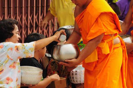 Chiang Khan, Thailandia - 16 luglio: Una non meglio identificata uomini d� cibo e fiore offerte a un monaco buddhista su 16 luglio 2011 in Chiang Khan, provincia di Loei, Thailandia. Thai tradizionale, persone far� fare al merito da dare cibo a Monaco