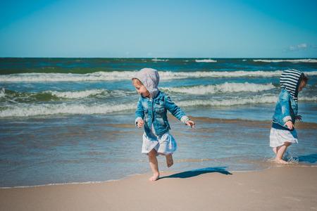 run away: two little girls run away from the waves