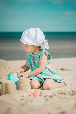 ittle: ittle girl digs holes in the sand on the beach