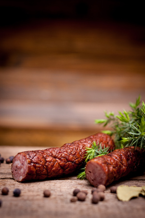tasty sausage and fresh juniper on old wooden table