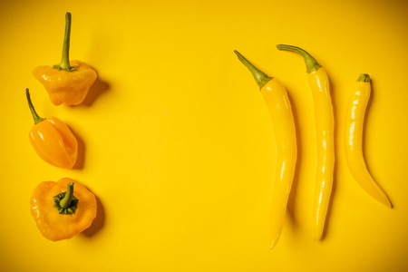 capsaicin: little spicy and fresh peppers on a yellow background Stock Photo