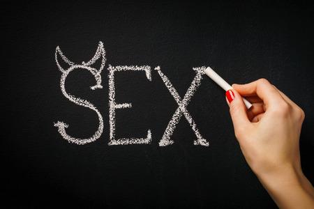 womans hand writing on the blackboard the word sex Foto de archivo