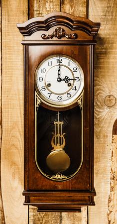 alte und große Uhr auf einer hölzernen Wand hängen