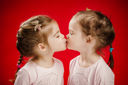 two beautiful twin sisters give each other a kiss Reklamní fotografie