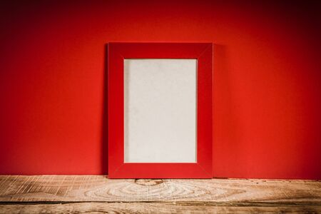 modern frame: old and wooden shelf with frame and red wall Stock Photo