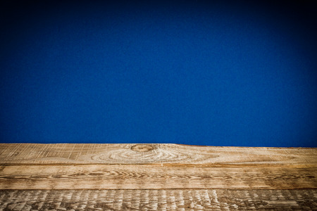 old and wooden shelf and dark blue wall