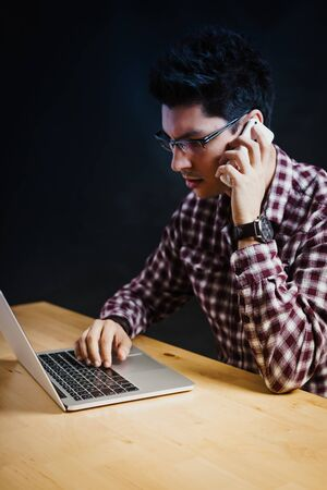 Programmer in the office working on the computer on a wooden desk