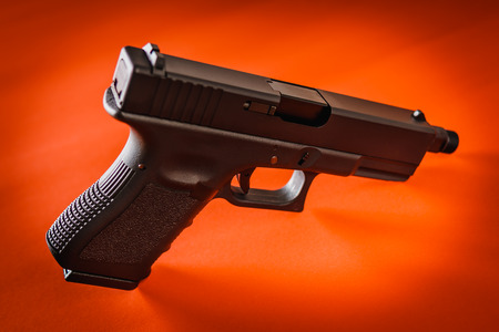 one black handgun on intense red background Stock Photo