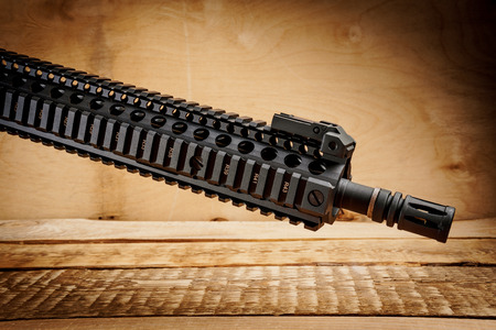 black assault rifle on an old wooden table