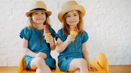 Twee kleine meisjes eten thuis een ijsje terwijl ze wachten op een zomervakantie Stockfoto