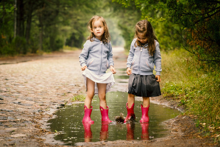 little girls pee Two little girls walk by the puddle in a summer forest