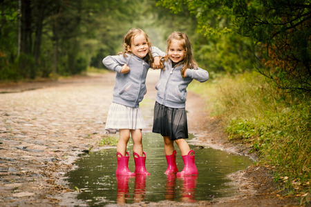 Two little girls walk by the puddle in a summer forest