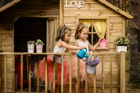 Two lovely girls play with watering can in a tree house in a summer forest Foto de archivo