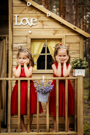 Two lovely girls in red dress posing in a tree house in a summer forest Stock Photo
