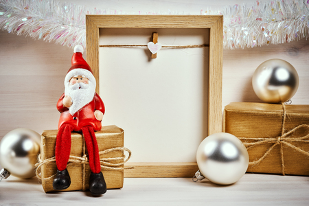 Christmas card with decorations on a wooden table with blank frame