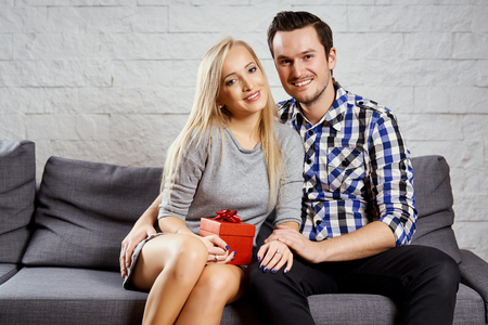young couple poses on a gray sofa at home Stock Photo