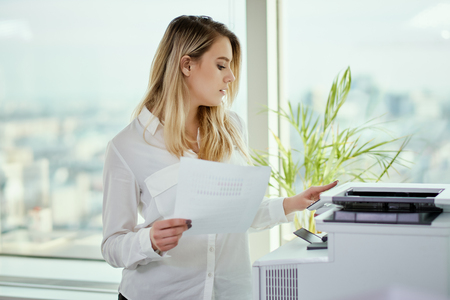 beautiful young businesswoman poses in a sunny skyscraper office Stok Fotoğraf - 94851684