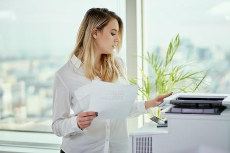 Schöne junge Geschäftsfrau wirft in einem sonnigen Wolkenkratzerbüro auf Standard-Bild - 94851684