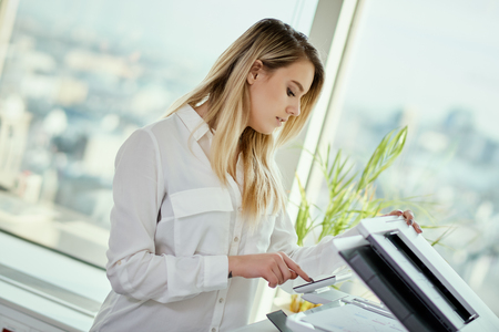 beautiful young businesswoman poses in a sunny skyscraper office