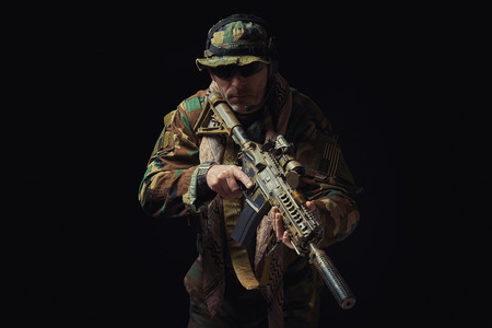 soldier of the American special forces in Afghanistan poses with a rifle on a black background Stock Photo
