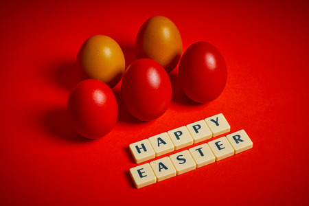 Easter decoration with colored eggs and text on a red background Archivio Fotografico