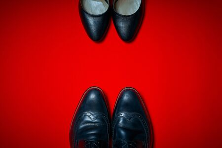 Top view of black high heels and mens shoes on an intense red background