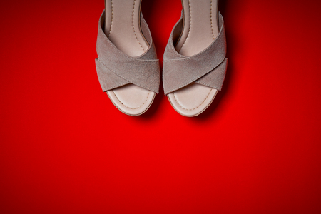 Top view of female beige shoes on an intense red background