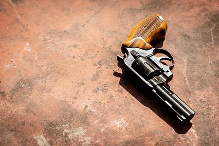 Black 9mm revolver on the concrete red backgroound