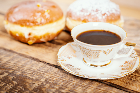cup of delicious and fragrant coffee with a tasty donuts on a wooden table Stock Photo