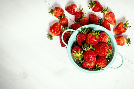 fresh red strawberries in a small colander on a white wooden table Zdjęcie Seryjne
