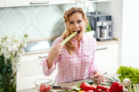 smiling woman holds and tastes fresh green celery in the kitchen 写真素材