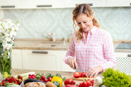 smiling woman in a shirt is slicing tomatoes on a kitchen table with vegetables Stock fotó