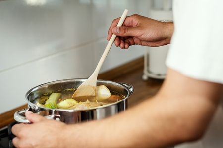 man mixes the delicious and fragrant broth in a pot on the gas stove in the kitchen